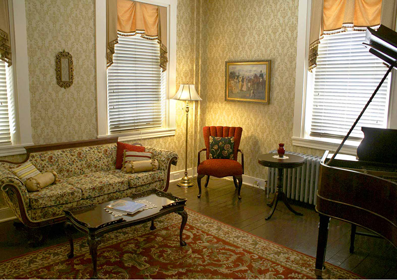 As you step back in time to the year 1855, our Formal Sitting Room welcomes you. Play the restored antique baby grand piano and enjoy the acoustics that hard wood floors and ten foot ceilings provide. Chat with new friends by the large windows looking out on the wrap-around porches and the front of the park.
